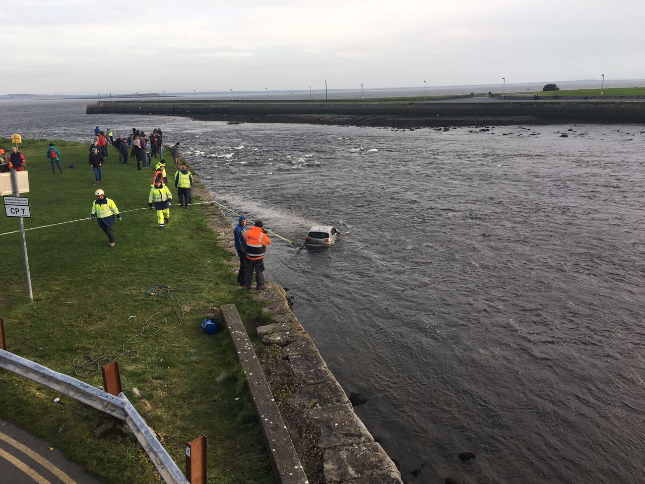 Passersby and emergency services gather on the Long Walk to watch the car as it is dragged from the Corrib